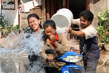A man pouring water on passers-by